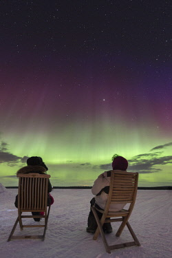 HMS2433346 Sweden, Norrbotten, Kiruna, two watchers on chair in front of northern light in swedish lapland
