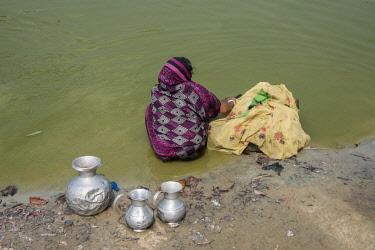 AS03CMI0012 Bangladesh, Chittagong, Maheshkhali Island (aka Mahesh Khali) Woman washing in pond.