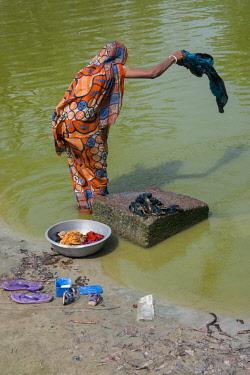 AS03CMI0013 Bangladesh, Chittagong, Maheshkhali Island (aka Mahesh Khali) Woman washing in pond.