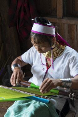 AS06KSU0610 Padaung (Kayan Lahwi) woman wearing brass neck coils weaving, Inle Lake, Shan State, Myanmar