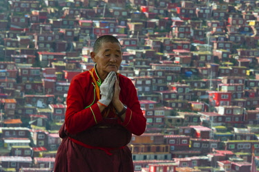 AS07KSU1658 Nun praying with the red log cabins lived by nuns and monks covering the mountain side in the background, Seda Larung Wuming, the world's largest Tibetan Buddhist institute, Garze, Sichuan Province, C...