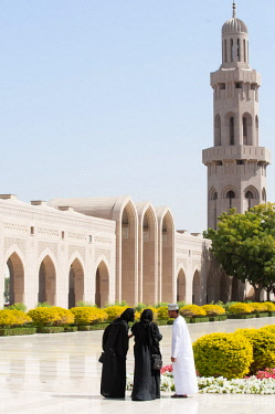 OMA2660 Middle East, Oman, Muscat.  An Omani man and two ladies visit The Sultan Qaboos Grand Mosque