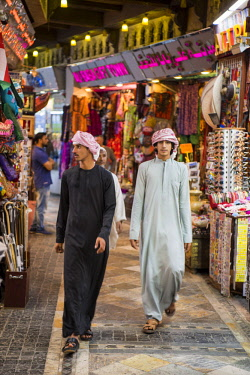 OMA2703 Middle East, Oman, Muscat.  Omani men stroll through one of the many narrow covered alleys in the old Muttrah Souk