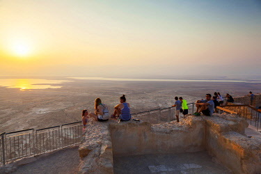 ISR0395 Israel, Dead Sea, Masada. Views from atop Masada with trekkers looking at the morning sun.