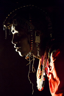 KEN11078AW Kenya, Maasai Mara, Maasailand. A Maasai man dressed with beaded necklaces, earrings, and ornaments and cloaked in his red shuka, sitting inside his darkened homestead early in the morning before the...