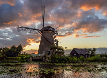 NLD0574AWRF Windmill in Kinderdijk at sunset, UNESCO World Heritage Site, South Holland, The Netherlands