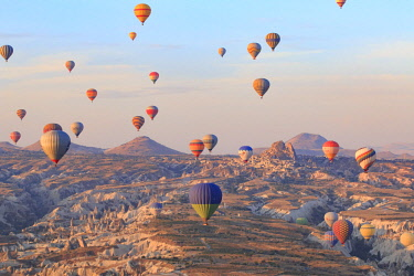 AS37EWI0532 Turkey, Anatolia, Cappadocia, Goreme. Hot air balloons flying above rock formations and field landscapes in the Red Valley, Goreme National Park, UNESCO World Heritage Site.