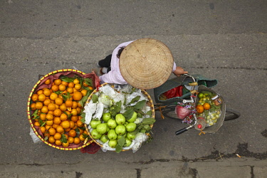 AS38DWA0420 Street vendor with round baskets of fruit on bicycle, Old Quarter, Hanoi, Vietnam