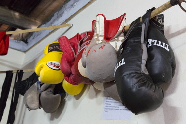 CA11BJY0157 Cuba, Havana. Boxing gloves hanging on wall in gym.
