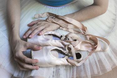 CA11BJY0219 Cuba, Havana. Close-up of ballerina holding toe shoes on lap.