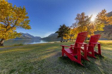 CN01CHA0135 Red Adirondack chairs along Upper Waterton Lake in Waterton Lakes National Park, Alberta, Canada