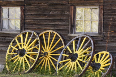 CN02BJY0117 Canada, British Columbia, Barkerville. Wagon wheels lean on old building.
