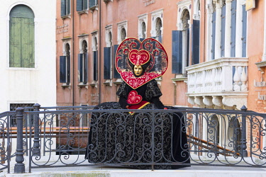 ITA12019AW Heart-shaped costume standing on a bridge at the Venice Carnival, Venice, Italy