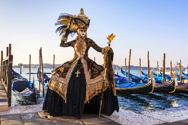 ITA12028AW A woman in a magnificent costume poses in front of Gondolas during the Venice Carnival, Venice Lagoon, St. Mark's Square,  Venice, Italy