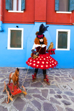 ITA12031AW A woman in a colourful costume poses with a toy dog in a street on Burano Island during the Venice Carnival, Burano,  Venice, Italy