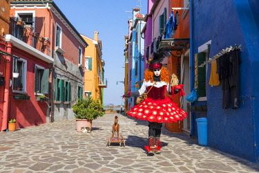 ITA12032AW A woman in a red costume walks a toy dog  in a street on the Island of Burano during the Venice Carnival, Venice, Italy
