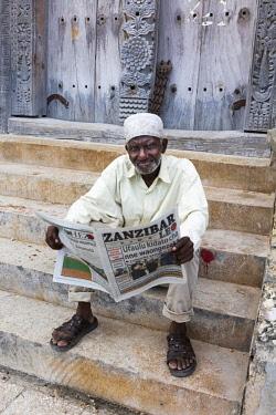 TZ3658AW An old man wearing a cap and kanzu sits on a step and reads the local Zanzibar newspaper, Stone Town, Zanzibar, Tanzania