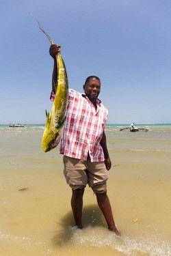 TZ3659AW A fisherman holds his catch with pride, Mkokotoni, Zanzibar, Tanzania