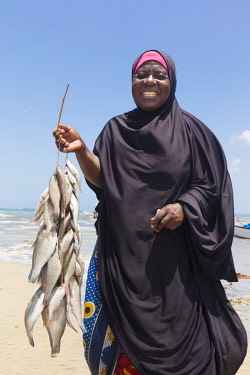TZ3660AW A woman wearing a buibui holds carries some fish to the market, Mkokotoni, Zanzibar, Tanzania
