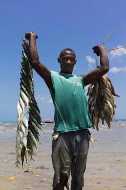 TZ3661AW A fisherman holds his catch with pride, Mkokotoni, Zanzibar, Tanzania