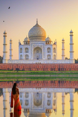 IND8506AW India, woman near the Yamuna river with the Taj Mahal reflecting in the river at sunset