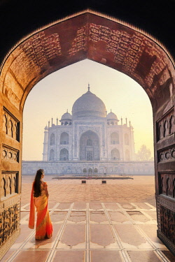 IND8520AW India, a beautiful woman in a red and yellow sari in front of the Taj Mahal at sunrise