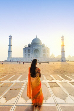 IND8522AW India, a beautiful woman in a red and yellow sari in front of the Taj Mahal at sunrise