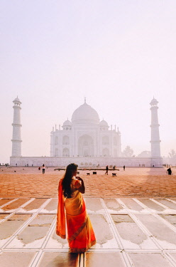 IND8523AW India, a beautiful woman in a red and yellow sari in front of the Taj Mahal at sunrise