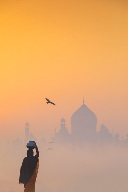 IND8528AW India, Agra.  Woman carrying a water jar on a foggy morning with the sun rising on the Taj Mahal