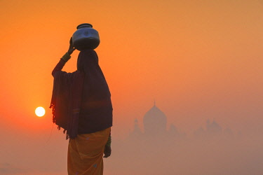 IND8530AW India, Agra.  Woman carrying a water jar on a foggy morning with the sun rising on the Taj Mahal