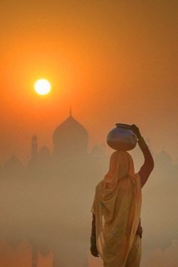 IND8532AW India, Agra.  Woman carrying a water jar on a foggy morning with the sun rising on the Taj Mahal