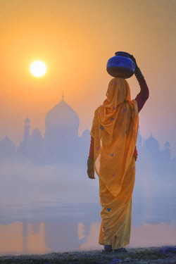 IND8533AW India, Agra.  Woman carrying a water jar on a foggy morning with the sun rising on the Taj Mahal