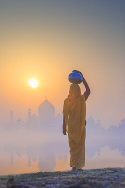 IND8534AW India, Agra.  Woman carrying a water jar on a foggy morning with the sun rising on the Taj Mahal
