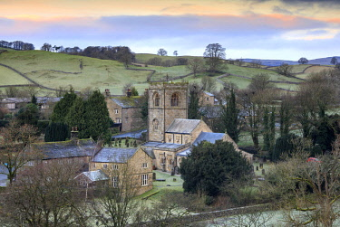 ENG15452AW England, North Yorkshire, Burnsall. St Wilfrid's Church and the village at sunrise.
