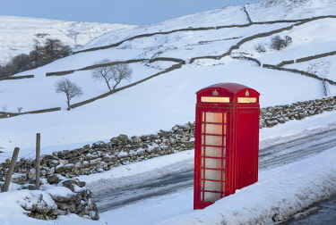 ENG15501AW England, North Yorkshire, Keld. Traditional red telephone box in winter landscape.