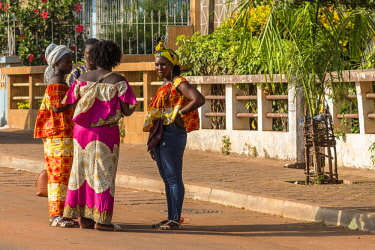 GUN0047AW Africa, Guinea Bissau. Bissau, ladies chatting on the street dressed up for Carnival