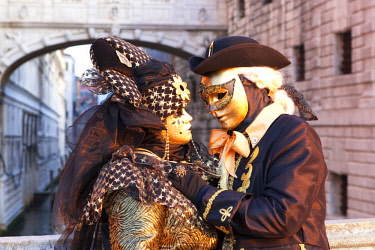 CLKDC80765 A couple of typical mask of Carnival of Venice with Bridge of Sighs on background, Venice, Veneto, Italy