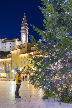 CLKGA80267 Close up of a tourist touching the christmas tree in Tartini square, Piran, Istria, Slovenia (MR)