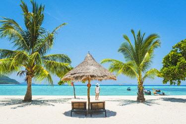 THA1312AW Ko Lipe, Satun Province, Thailand. Tourist admiring the view on a white sand beach (MR).