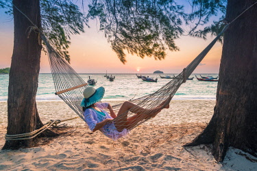 THA1325AW Ko Lipe, Satun Province, Thailand. Woman lying on hammock on the beach enjoying the sunrise (MR).