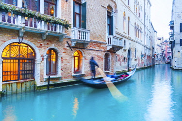 ITA12180 Venice. Veneto. Italy. Gondola rowed on a canal surrounded by palaces.