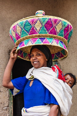 ETH3460 Ethiopia, Amhara Region, Ankober.  An Amhara woman with a traditional woven basket on her head. These baskets are used for carrying the staple round Ethiopian flat bread called injera, which is made f...