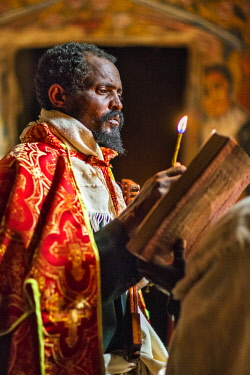 ETH3491 Ethiopia, Tigray Region, Tembien.  A priest at Gebriel Wukien ancient rock-hewn church reads a passage from the bible with the aid of a taper.
