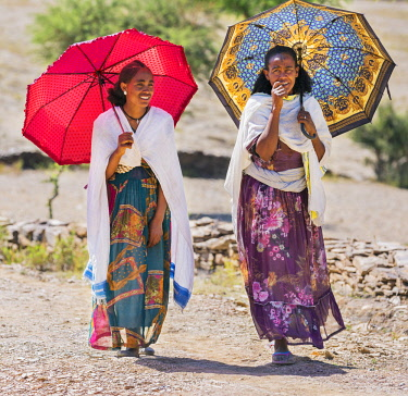 ETH3495 Ethiopia, Tigray Region, Nebelet.  Two Tigray women walk to market. The lady on the right has a cross tattooed on her forehead to denote her Christianity. This practice is still common in rural areas.