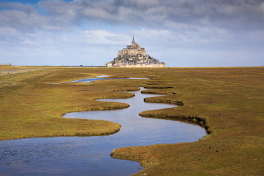 FRA10324AW A meandering pool of water leads to Mont Saint Michel, Manche, Normandy, France