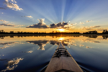 US27CHA3694 Kayaking into sunset rays on McWennger Slough near Kalispell, Montana, USA