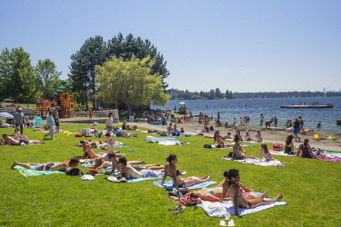 US48JME0758 USA, Washington State, Kirkland, sunbathers on grass in Marsh Park on Lake Washington