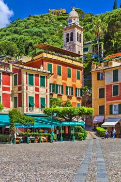 ITA12549 Bell tower of Chiesa di San Martino and restaurants in Piazza Martiri dell Olivetta, Portofino Harbour and Marina, Portofino, Paraggi, Liguria, Italy.