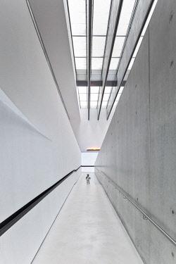 ITA12553 A 3 year old caucasian boy walks up a ramp in the interior of the MAXXI Museum designed by the Architect Zaha Hadid, Flaminio, Borgata Ottavia, Rome, Lazio, Italy. MR