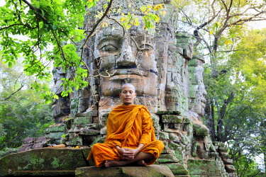 CMB1622AW Southeast Asia, Cambodia, Siem Reap, Angkor temples, Buddhist monk in saffron robes meditating (MR)